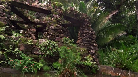Tracking shot overlooking a stone columned structure in the Jardim Botanico, Rio Footage