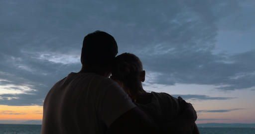 Loving couple looking at sea and sky in the evening Footage