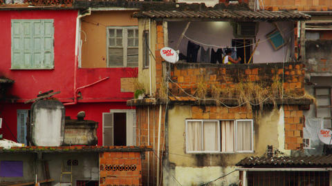 Slow motion static footage of a colorful, run-down favela and a woman Footage