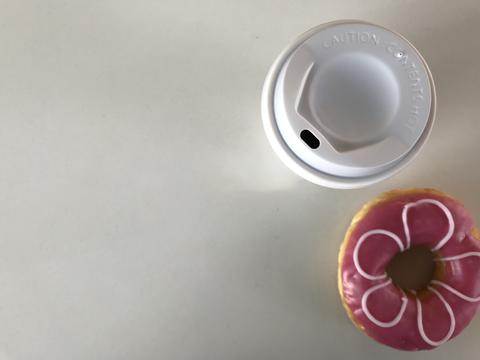 top view of flower-like pink doughnut and plastic cup of coffee フォト