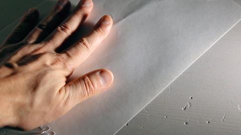 A man's hand crumples a sheet of white paper Live Action