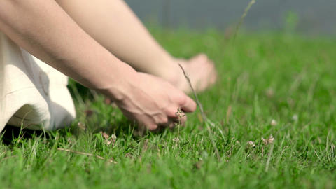 A girl sits on the green grass by the river GIF