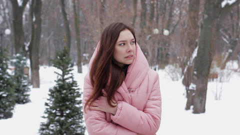 A beautiful woman tries to warm her frozen hands with her breath on a winter Footage