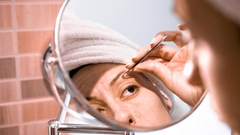Adult woman corrects eyebrows and looking in the mirror Stock Video Footage