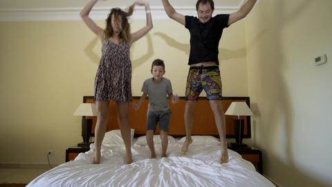 Happy family jumping on the bed. Happy family concept. Father, mother and little Footage