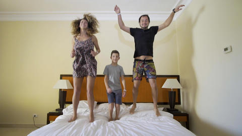 Happy family jumping on the bed. Happy family concept. Father, mother and little Live Action