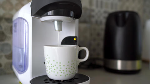 Home capsule coffee machine prepares a cup of fresh coffee with milk Footage