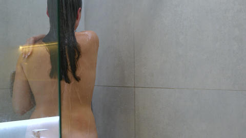 Woman washes her hair, shoulders, arms and back in the shower. Hair care, beauty Live Action