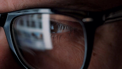 Man in glasses looking on the monitor and surfing Internet. The monitor screen Live Action