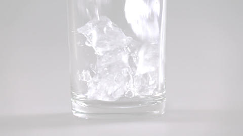 Close up of ice cubes falling into glass slow motion Footage