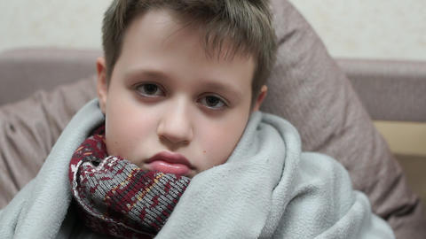 A cold boy looks sadly at the camera. He has the flu Footage