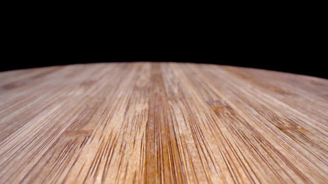 Bamboo cutting board extreme closeup dolly from back to front with hole in board Live Action