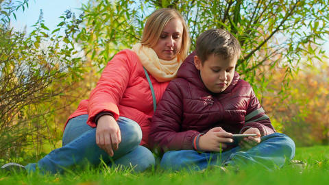 Teen boy sitting on the grass and playing smartphone. Sitting next to mom Live Action