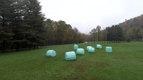 Aerial Drone - Fly Over Field With Plastic Wrapped Bales of Hay in Fall in Footage