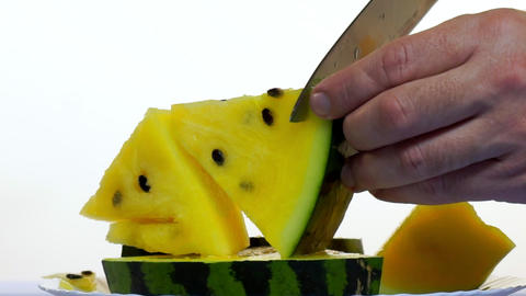 A man's hand cuts a juicy yellow watermelon into pieces Footage