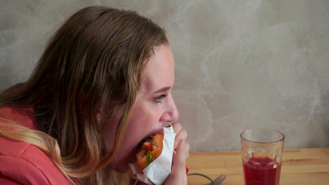A young hungry girl eating a hamburger. Sitting at a table in a cafe. Slow mo Footage