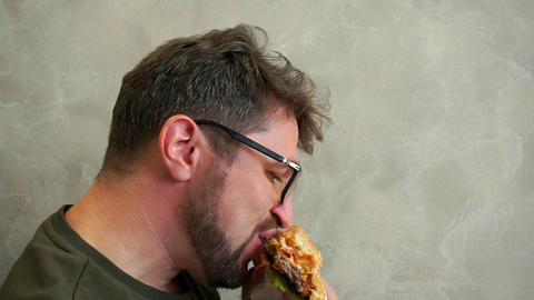 Hungry bearded man with glasses eating a delicious hamburger. Slow-mo Footage