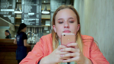 Young attractive girl looking smartphone in cafe. She's upset Footage