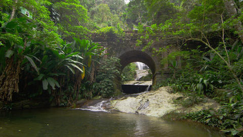 Tracking shot of jungle stream, waterfall seen through stone arch Footage