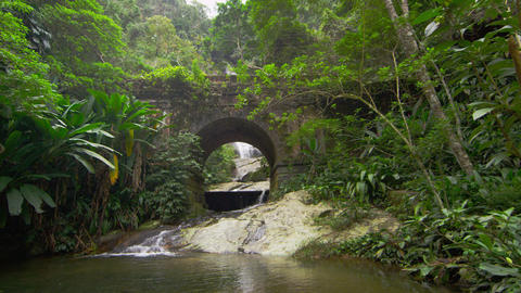 Tracking shot of jungle stream, waterfall seen through stone archway Footage