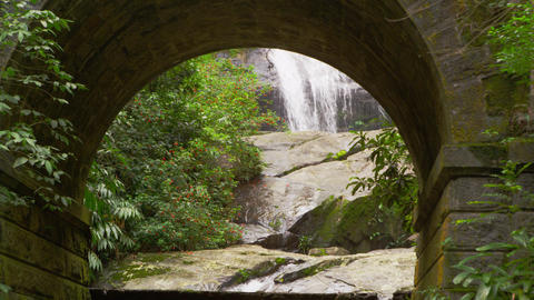 Tracking shot of a waterfall through a sone arch Footage