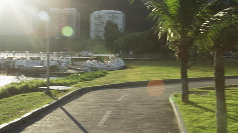 Slow-mo, tracking shot of people biking along the Lagoa in Rio De Janeiro Footage