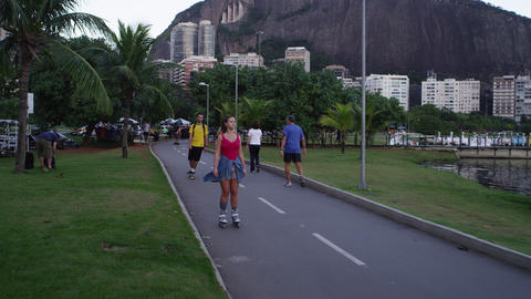 RIO-JUNE 18: People rollerbla bike, and walk along lake Lagoa at dusk on June 18 Footage