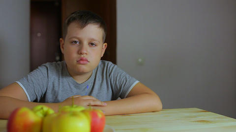 Sad boy sitting at the table. He doesn't want to do his homework. Schoolboy lazy Footage