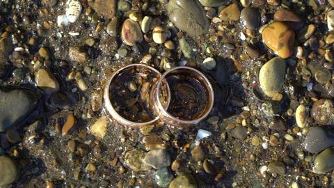 Two gold wedding rings lying on beach stones shining on sun light close up macro