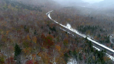 Aerial Drone - Fly Over Forest With Remnant of Fall Colors During Driving Snow Footage