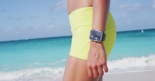 Jogger In Sportswear Wearing Smartwatch Walking At Beach During Summer Live Action