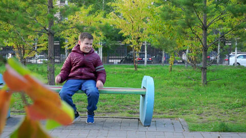Happy boy sitting on a bench in the Park and laughing in park. Slow mo Footage