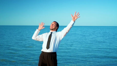 Excited businessman screaming and raising hands to the sky by the sea, slow Footage