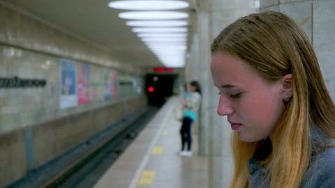 Girl with a smartphone in the subway. Portrait of young girl looking at phone Footage