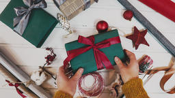 Christmas gift giving - someones hand in red knitted sweater making bow on red Footage
