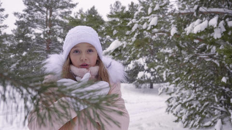 White girl is cold and claps her hands while snowfall in winter forest GIF