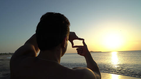 Young man with curly hair making photo frame with his hands at amazing sunset on Footage