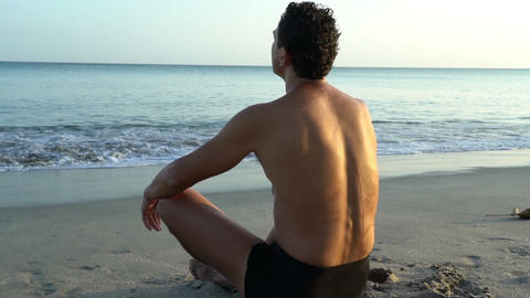 Young caucasian man relaxing on the beach near calm sea, close-up of hands, gyan Footage