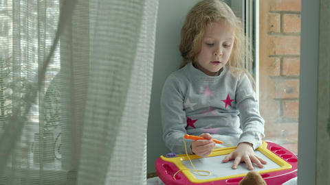 A little girl with red wavy hair sits on the windowsill and draws on a magnetic Live Action