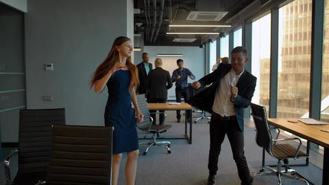 Couple in business office dancing after winning deal celebrating Archivo