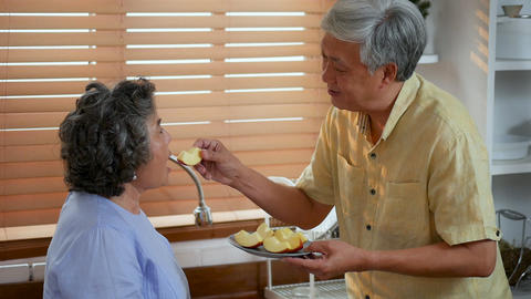 Asian senior couple eating apple fruit in kitchen at home ビデオ