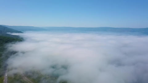 Flying above the clouds. Coast of Lake Baikal. Mountains covered with forest. GIF