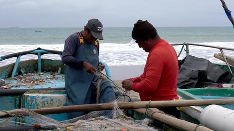 San Pedro, Ecuador - 20180915 - Two Men Fix Two Nets Live Action