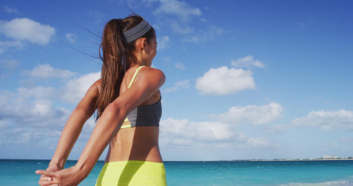 Determined Jogger Stretching Hands While Exercising At Beach In Summer Live Action