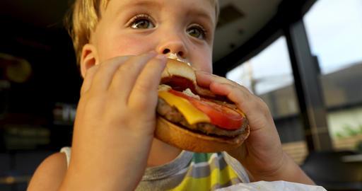 Kid eating hamburger. Fast food concept Footage