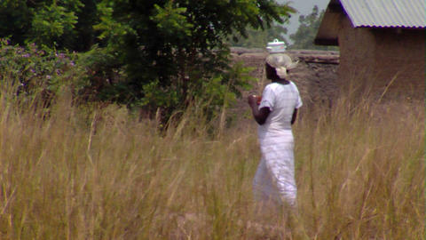 African woman walking through a grassy field Footage