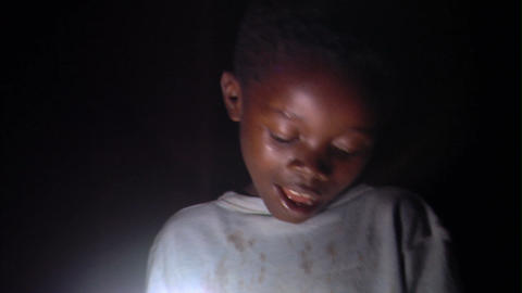 Small boy reading by a lamp in Africa Live Action