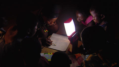 African kids reading by a lamp Live Action