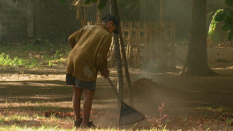 Man raking leaves in Bali Footage