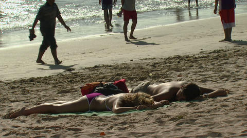Two people sunbathing on a beach in Bali Footage